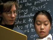 Teacher and child in front of blackboard