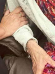 Carer holding elderly persons' hand